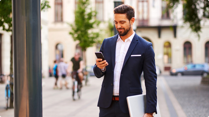 Business man with a laptop stopped on a sidewalk to check his phone, smiling, with a busy city scene in the background.