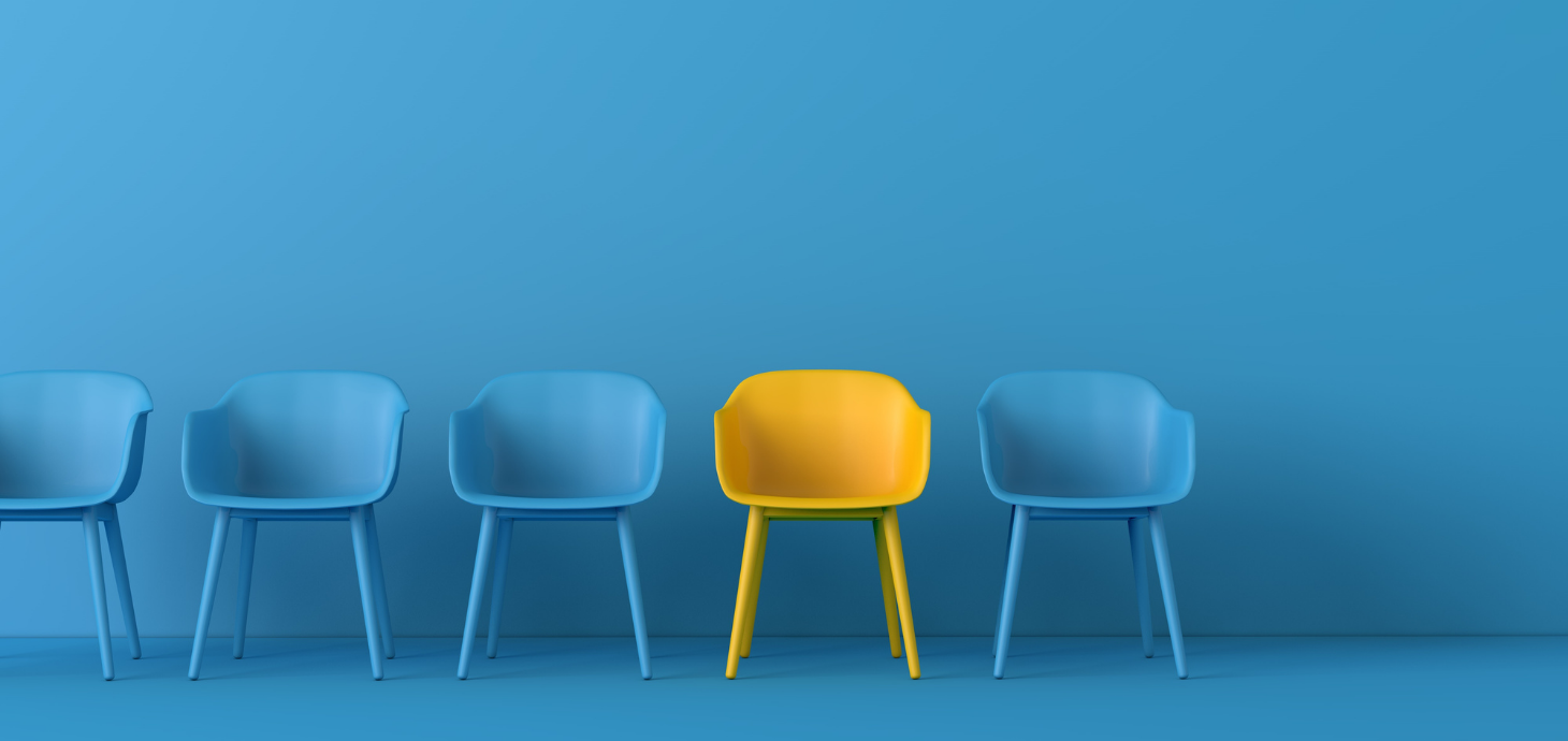 One yellow chair amidst four blue chairs on a blue background.