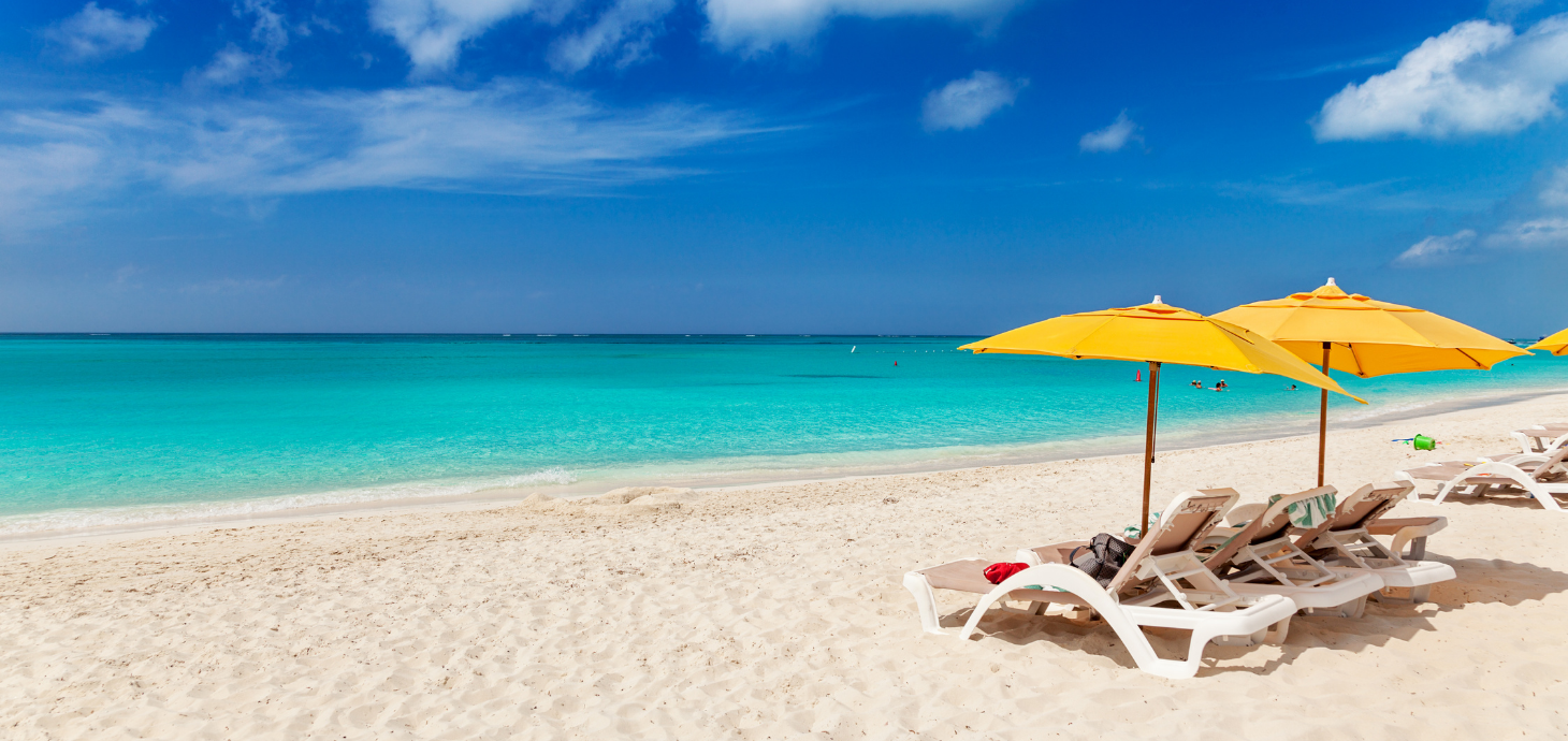 Two beach chairs and two yellow umbrellas on a beach.