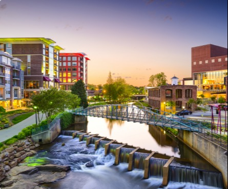 Greenville city view at sunset, with pedestrian bridge over a river and waterfalls.